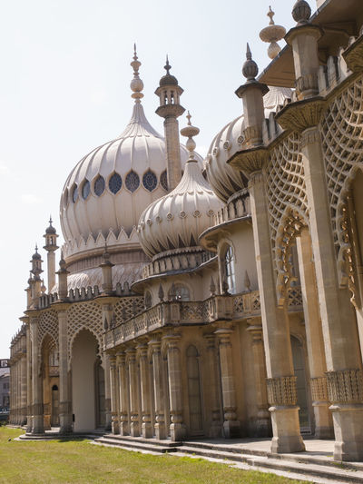 Royal Pavilion Brighton Sussex England The Royal Pavilion, also known as the Brighton Pavilion, is a former royal residence located in Brighton, England. Beginning in 1787, it was built in three stages as a seaside retreat for George, Prince of Wales, who became the Prince Regent in 1811. It is built in the Indo-Saracenic style prevalent in India for most of the 19th century. The current appearance of the Pavilion, with its domes and minarets, is the work of architect John Nash, who extended the building starting in 1815 Architectural Feature Architecture Brighton Pavilion Building Exterior Built Structure Façade Famous Place History John Nash Minarets Outdoors Place Of Worship Prince Of Wales, Royal Pavilion Royal Pavilion Gardens Spire  Travel Destinations