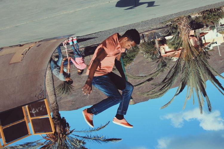 Tilt image of young man practicing stunt at skateboard park