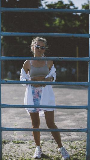Full length portrait of woman standing against railing