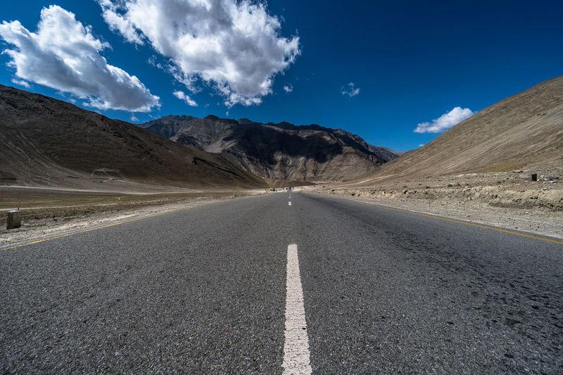 Empty road amidst desert against sky