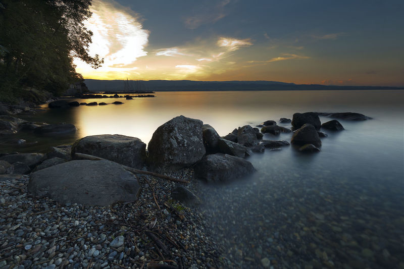 Sunset at Lake Leman, town of Yvoire, France. Water Sky Sunset Rock Solid Scenics - Nature Beauty In Nature Rock - Object Tranquility Cloud - Sky Tranquil Scene Nature Sea No People Idyllic Beach Outdoors Reflection Yvoire France Lake Leman Dawn Dusk Colorful Sunrise