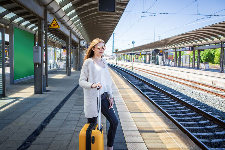 Young Woman With Luggage Waiting At Railroad Station Platform