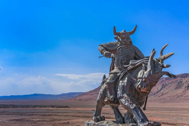 Statue on desert against blue sky