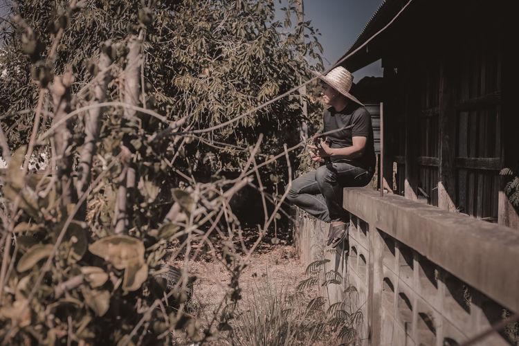 Man wearing hat playing guitar sitting on railing