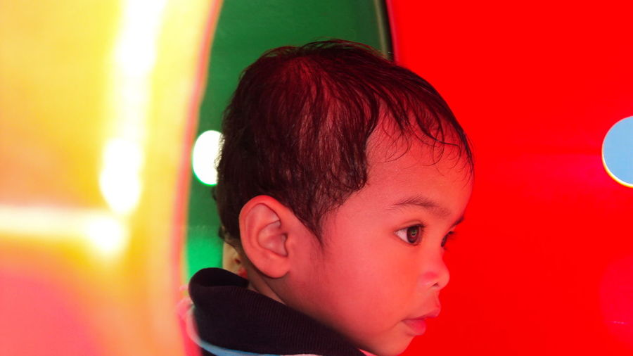 Close-Up Of Boy Looking Away While Playing In Tube Slide