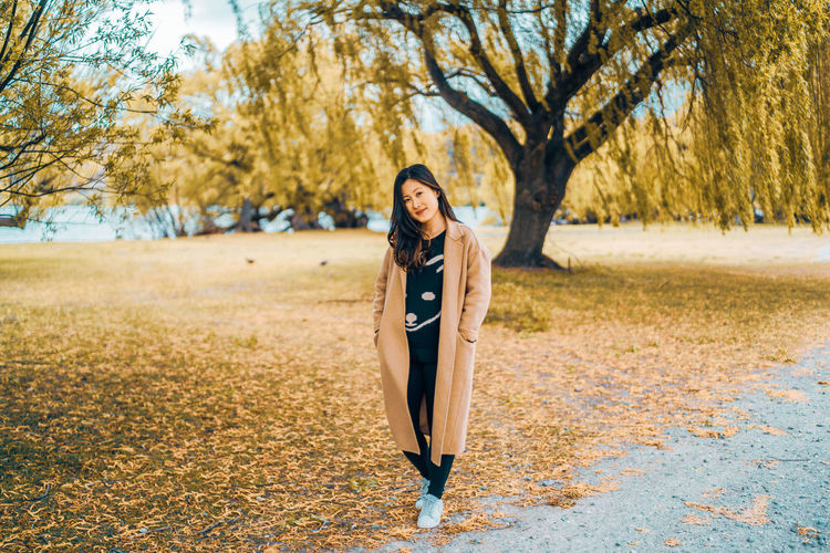 Portrait of young woman standing on field during autumn