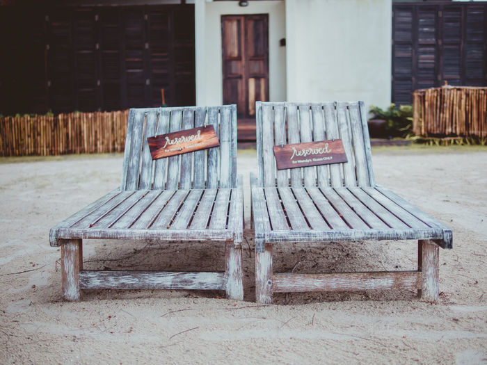 Chairs on bench against brick wall