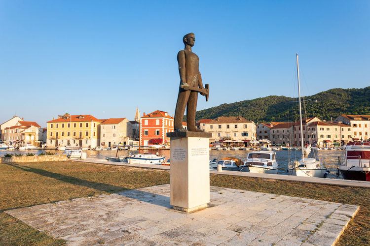 Male statue at harbor in city against clear blue sky