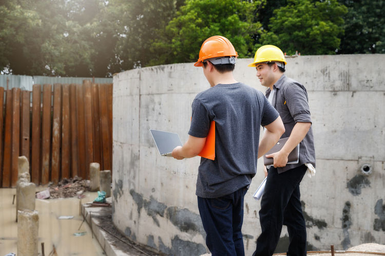 Architects walking by wall at site