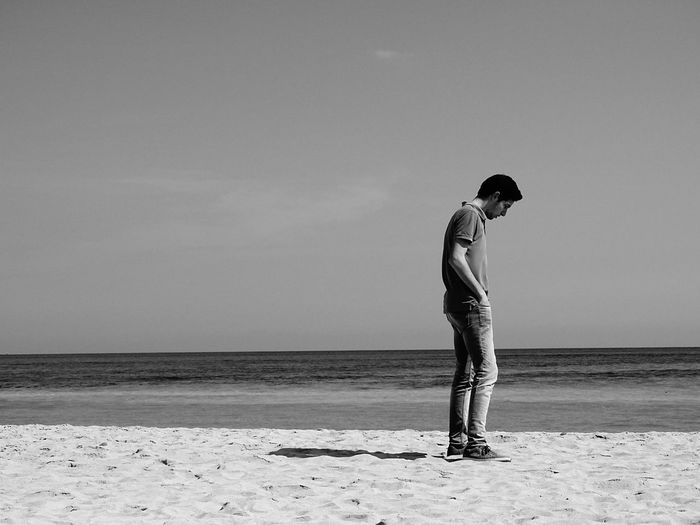 Full length of man looking down while standing at beach against sky