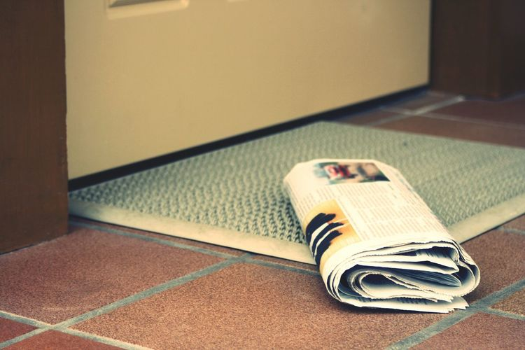 Close-Up Of Newspaper On Tiled Floor
