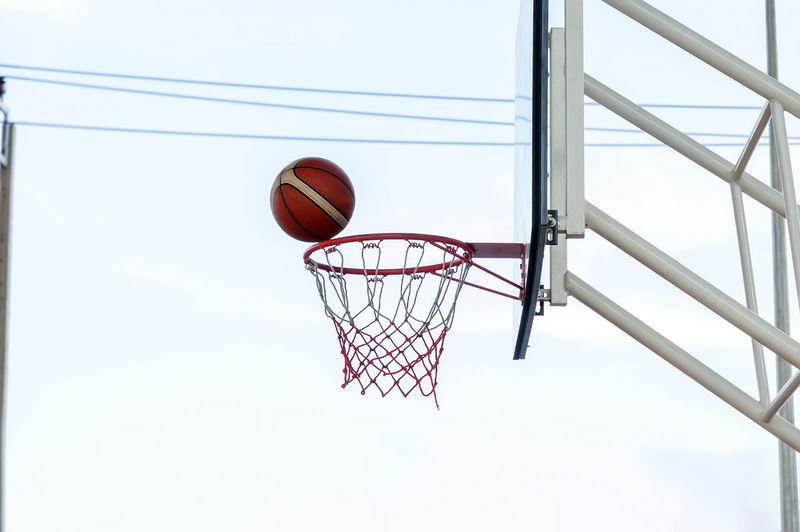 Low Angle View Of Basketball Hoop Against Sky Basketball - Sport Basketball Hoop Sport Low Angle View Ball Basketball - Ball Sky Day Net - Sports Equipment Nature Red No People Playing Metal Outdoors Motion Leisure Activity Court Making A Basket Taking A Shot - Sport