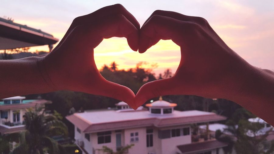 Cropped hands of woman making heart shape during sunset