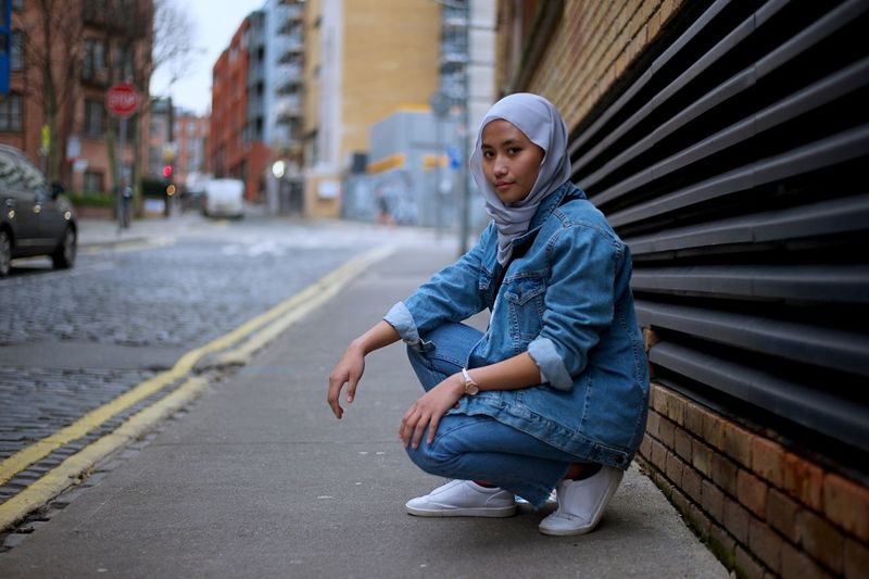 Portrait of woman in hijab crouching on footpath