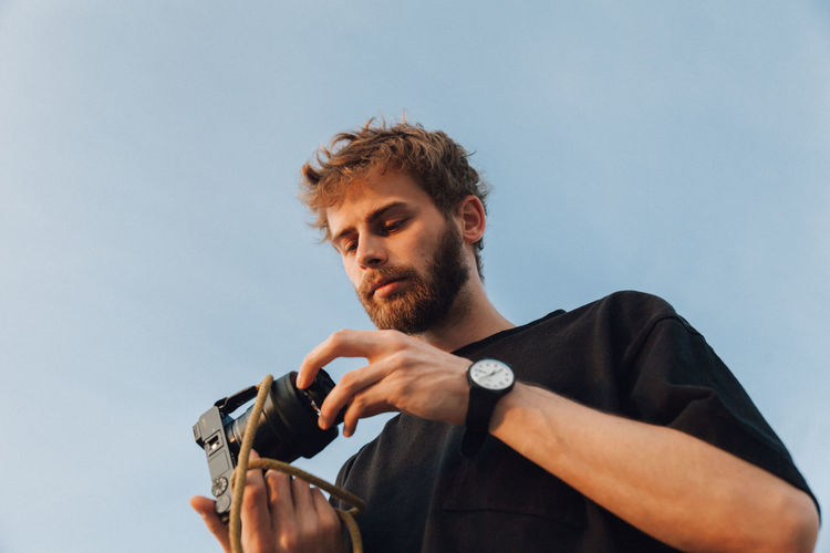 Portrait of young man holding camera against sky