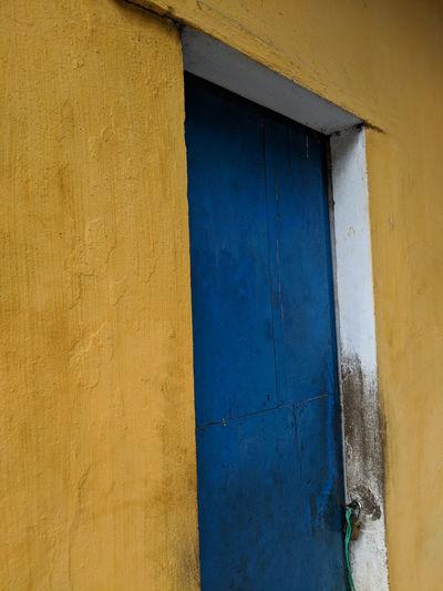 Blue door, yellow wall, streets of hoi an, vietnam.