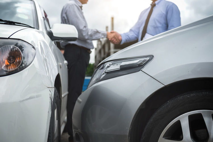 Midsection of customer shaking hands with car dealer outdoors