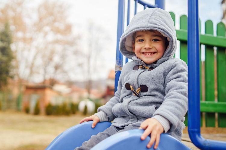 Portrait of smiling boy sitting on slide at playground