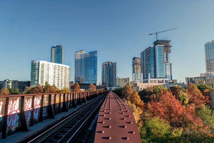 Railway bridge in city against clear blue sky