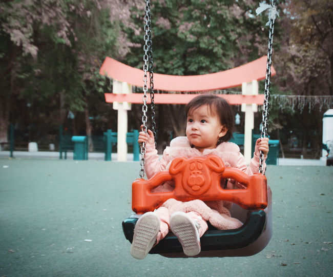 Cute girl sitting on swing at playground