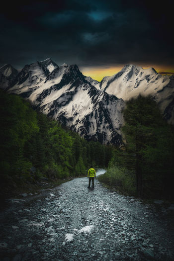 Rear view of man walking on dirt footpath leading towards snowcapped mountains at night