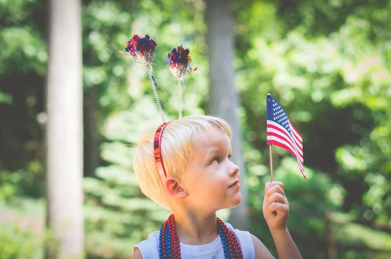 Close-Up Of Girl Holding American Flag During Independence Day