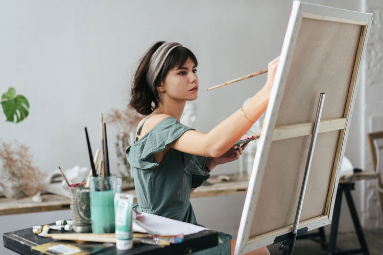 Artist Lifestyle Painter - Artist Painter One Person Paintbrush Brush Creativity Holding Art And Craft Indoors  Occupation Easel Studio Young Adult Real People Casual Clothing Palette Artist's Canvas Standing Waist Up Art Studio Art Class Hairstyle