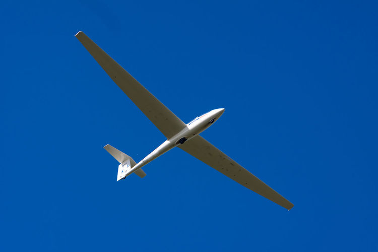 Glider against blue sky Aeroplane Aerospace Industry Air Vehicle Airplane Blue Clear Sky Day Flying Glider Journey Low Angle View Mid-air Mode Of Transport Nature No People Outdoors Sky Sports Transportation Travel