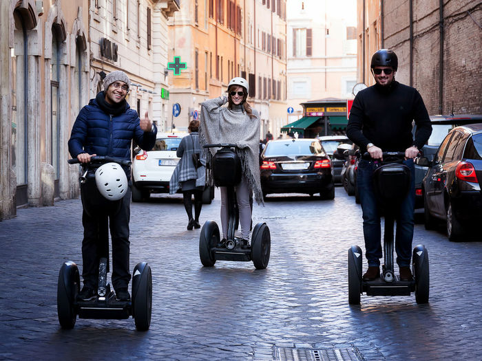 Rome, Italy - November 27, 2016: Boys Segway through the narrow streets of central Rome. Mission Moving Around Rome Road Adult Architecture Biker Building Exterior Built Structure City Day Full Length Helmet Land Vehicle Lifestyles Men Mode Of Transport Motorcycle Outdoors People Real People Riding Segway Street Transportation