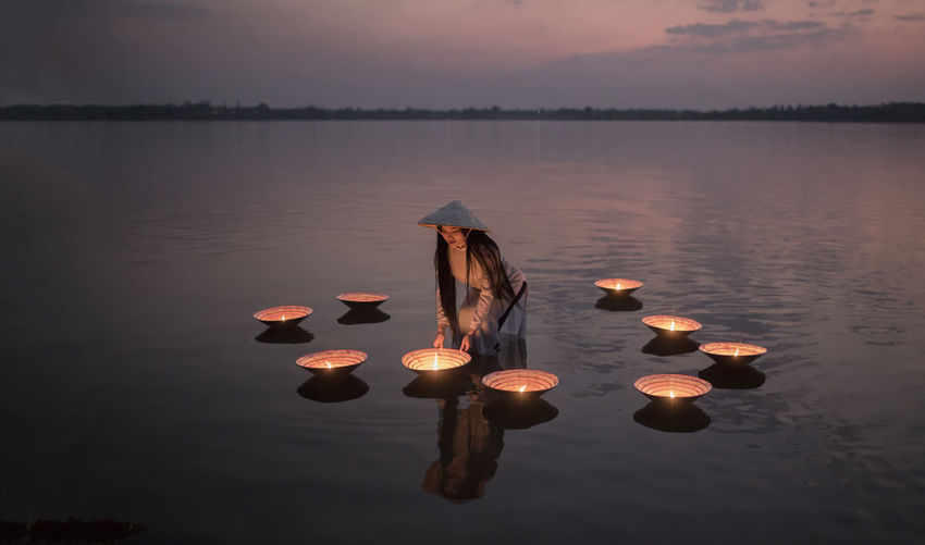 Women wearing Ao Dai Vietnam traditional dress with lamp in the lake at sunset ASIA Sunset_collection Thailand Vietnam Vietnamese Ao Dai Beauty In Nature Culture Day Fire Lake Lake View Lamp Nature No People Outdoors Portrait Reflection Scenics Sky Sunset Tranquil Scene Tranquility Water Women