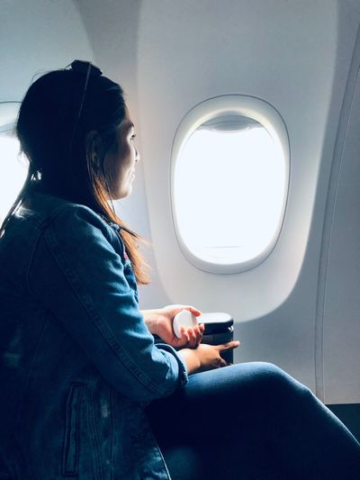 Side view of woman sitting in airplane