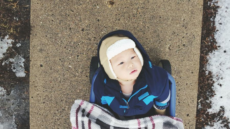 Directly Above View Of Toddler In Baby Carriage On Footpath