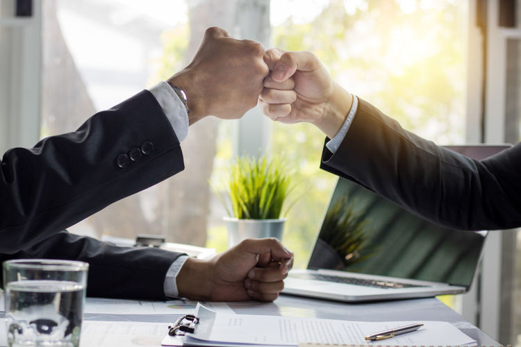 Cropped image of colleagues fist bumping in office