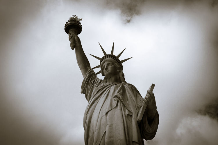 Low Angle View Of Statue Of Liberty Against Cloudy Sky