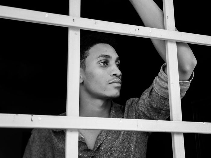 A young man looks through a window