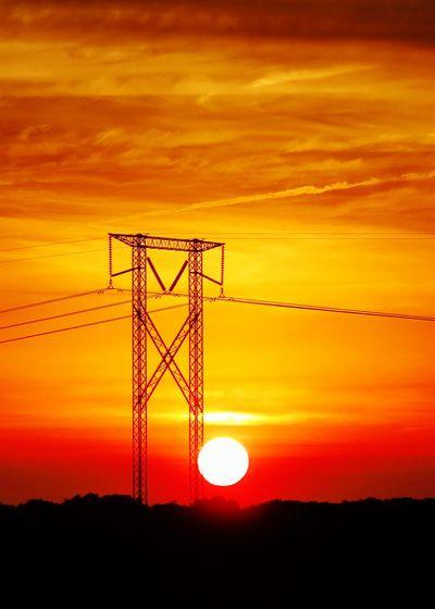 Electricity Pylon On Silhouette Landscape At Sunset