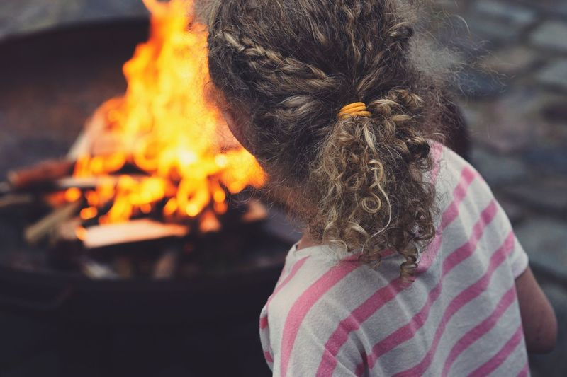 Rear View Of Girl Standing By Fire Pit At Back Yard