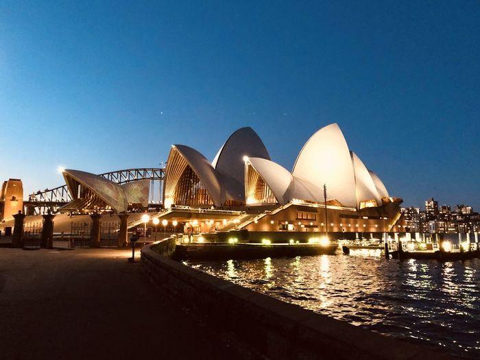 Illuminated bridge against clear blue sky at night