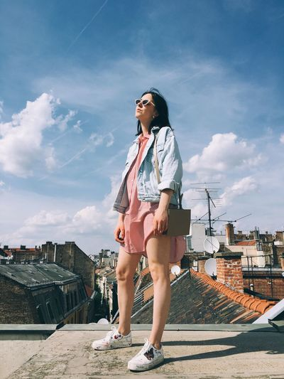 Full length of young woman standing against sky in city