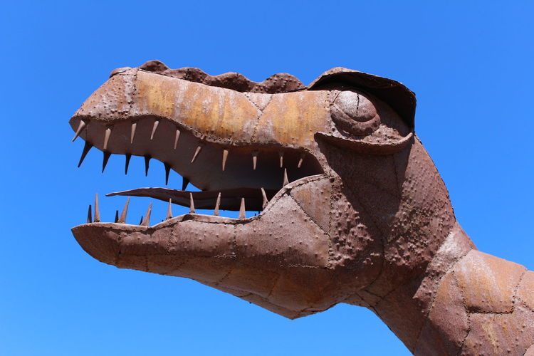 Low angle view of metal sculpture of dinosaur