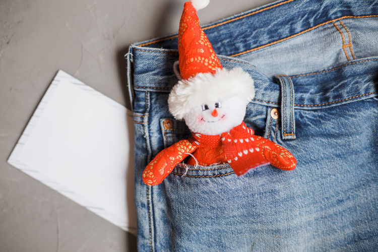 Merry Christmas and a happy New Year card with snowman in the jeans pocket