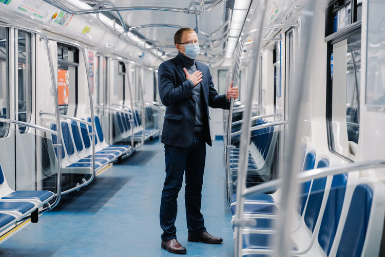 Businessman wearing mask while standing in train