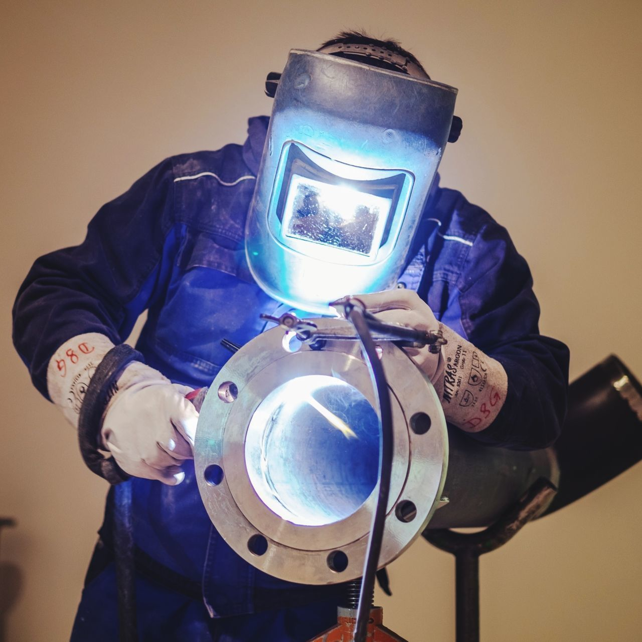 one person, real people, indoors, men, front view, holding, three quarter length, protection, blue, obscured face, mask, protective workwear, security, standing, occupation, safety, metal, disguise, waist up