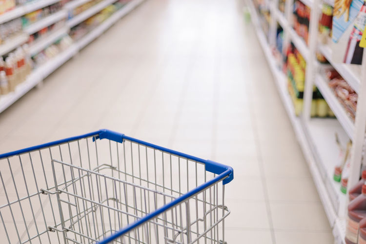 Concept image of buying. Shopping trolley in a Tesco Hypermarket with blurry background of groceries on the rack. Focused only at the trolley. Tesco  Supermarket Hypermarket Shopping Shopping Cart Shopping Mall Trolley Store Retail  Choice Consumerism Indoors  Shelf Customer  Variation Groceries Lifestyles Food And Drink Aisle Buying Empty Market Choosing Focus On Foreground Flooring Tiled Floor
