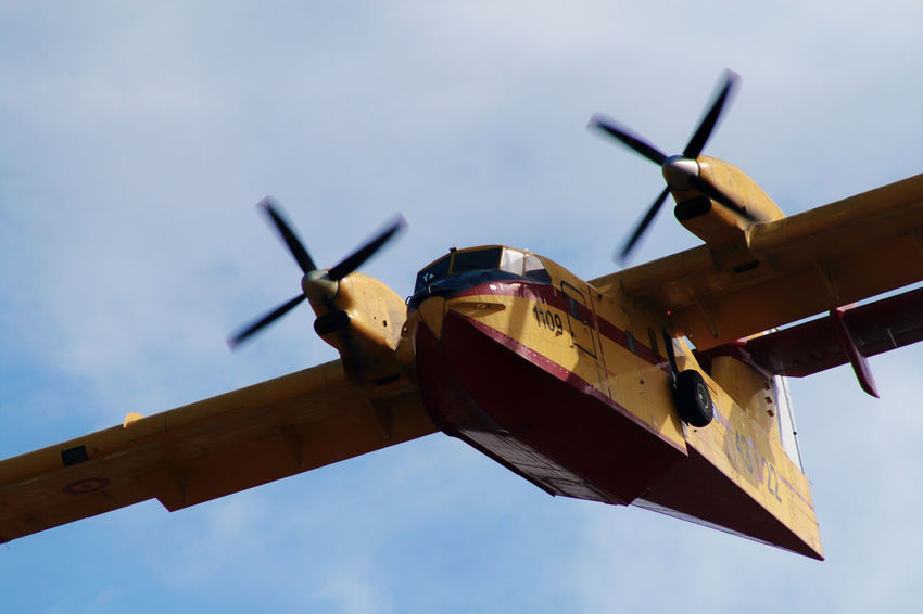 Air Force Air Vehicle Airplane Airshow Blue Canadair Cloud - Sky Day Fighter Plane Firefighter FireFighting  Flying Mid-air Military Military Airplane No People Outdoors Red Sea Sky Water Yellow