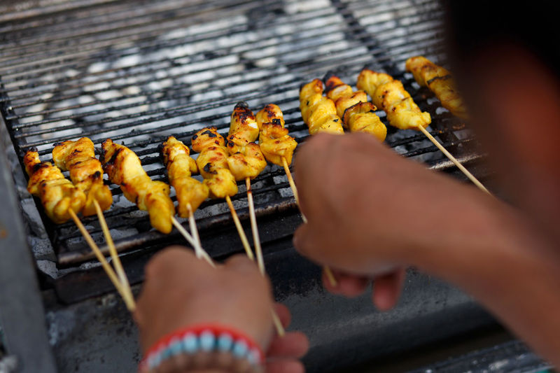 Cropped hands of person making satay on barbeque grill