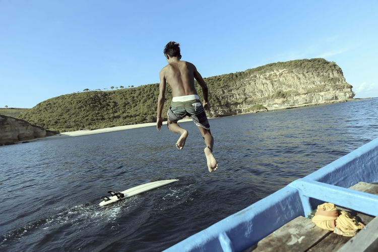 Full length of shirtless man jumping in sea against sky