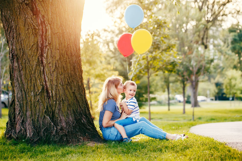 Woman kissing son with balloons against tree at park