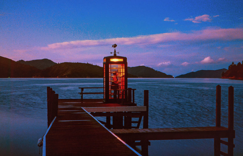 Man in telephone booth on pier by sea during sunset