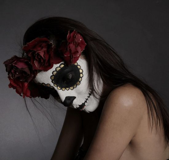 Side View Of Shirtless Woman With Spooky Face Paint Against Gray Background